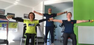 People with MS doing exercise in the gym - lateral raise with objects or weights